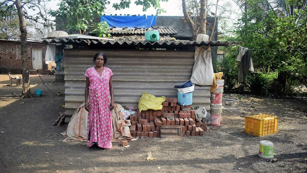 Domestic worker in a pink dress standing in front of a tin home and pile of bricks