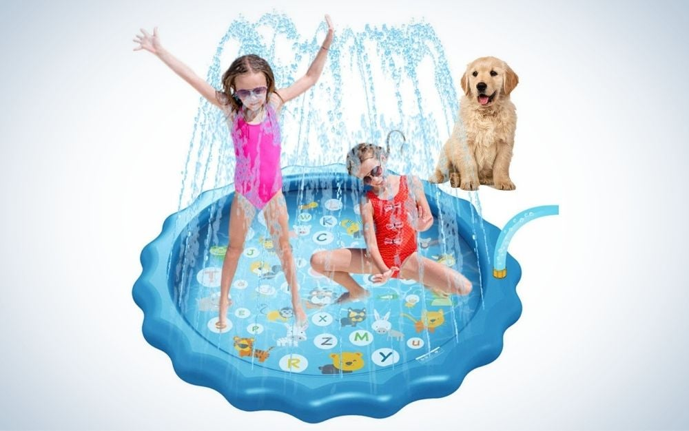 Two little girls playing on a blue splash pad and a dog looking at them