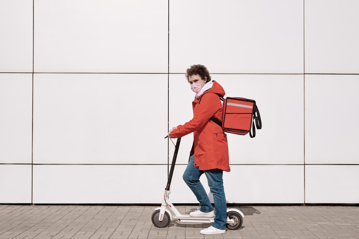 A person wearing a mask rides a scooter