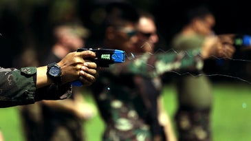 Military member shooting a blue Taser
