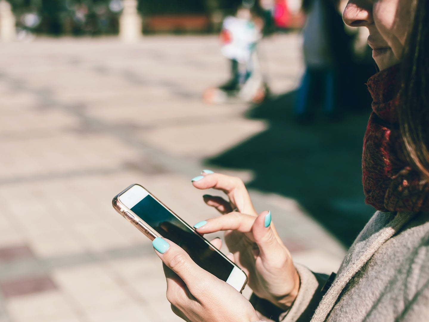 A person standing on a sidewalk outside while using their phone.