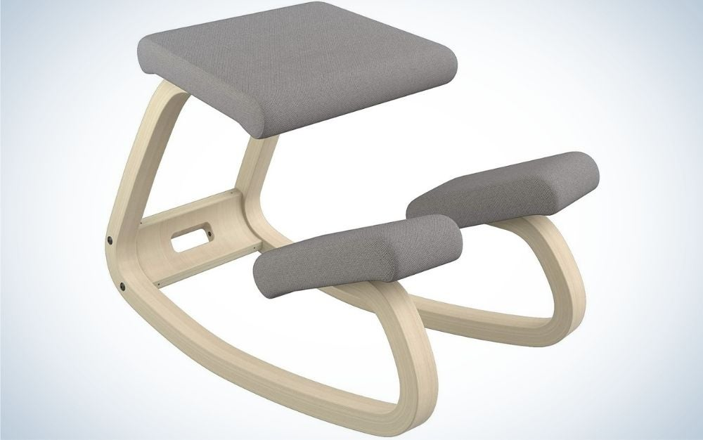 A beige kneeling chair with grey seats and two supportive pieces of the chair.
