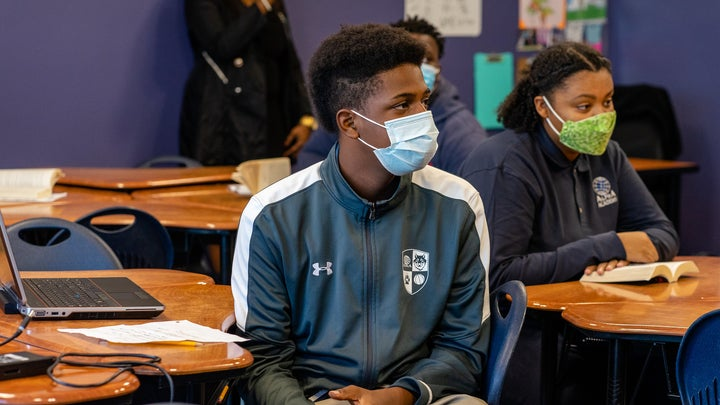 Black students in masks and track suits at desks