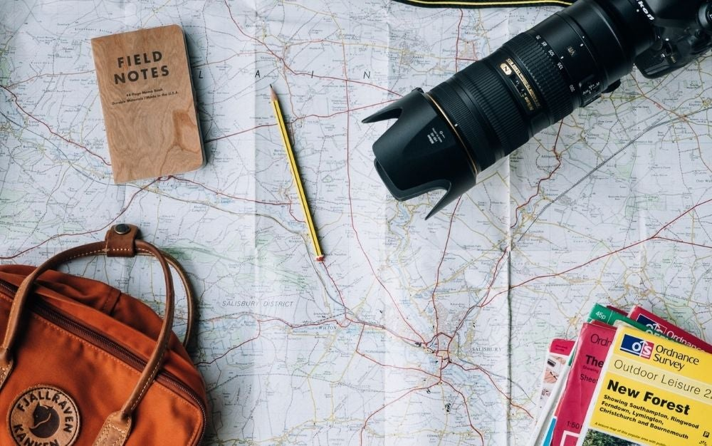 A map with the directions of the roads and over it a pencil, a professional camera, a notebook, and an orange bag.