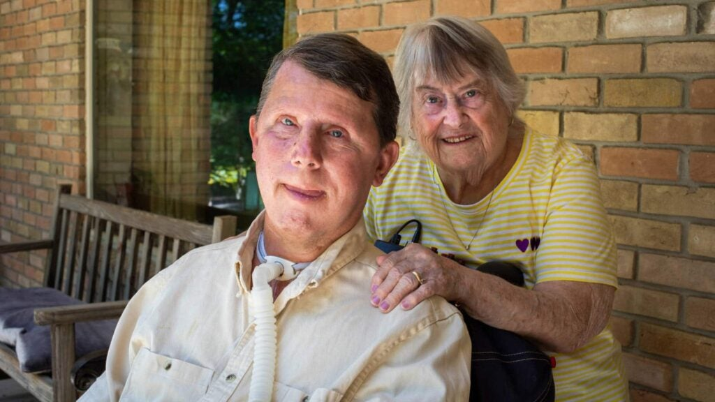 Muscular dystrophy survivor David Taylor with his ventilator and mother Dorothy on porch