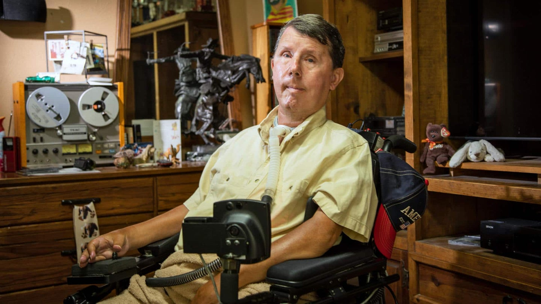 Muscular dystrophy survivor David Taylor in a wheelchair in his Texas house