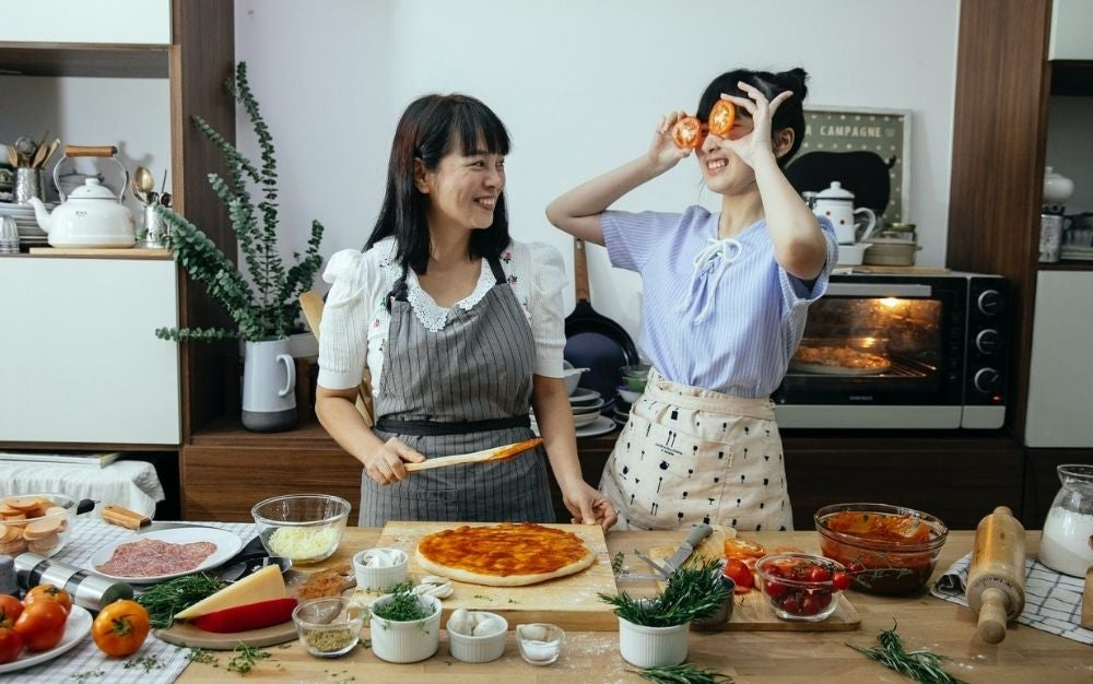 Two woman laughing with each other while cooking pizza in the kitchen.
