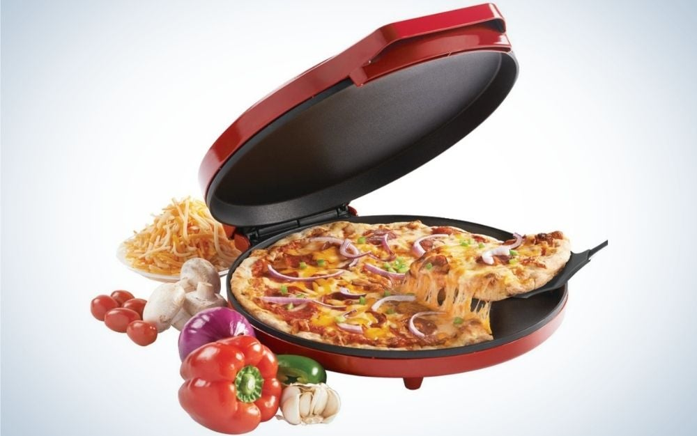 A red metal pizza oven with a pizza into it and some vegetables on his side.