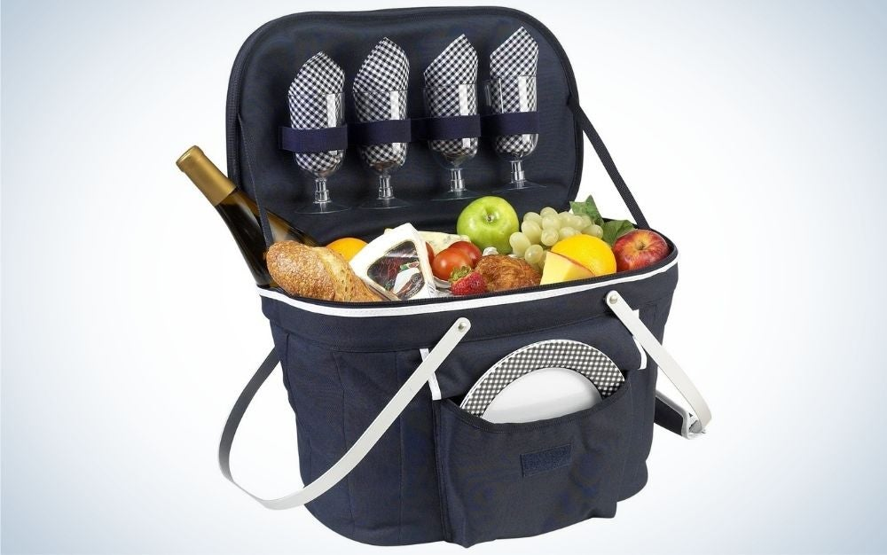 Navy picnic basket with padded handles filled with plate, wine glasses, and food