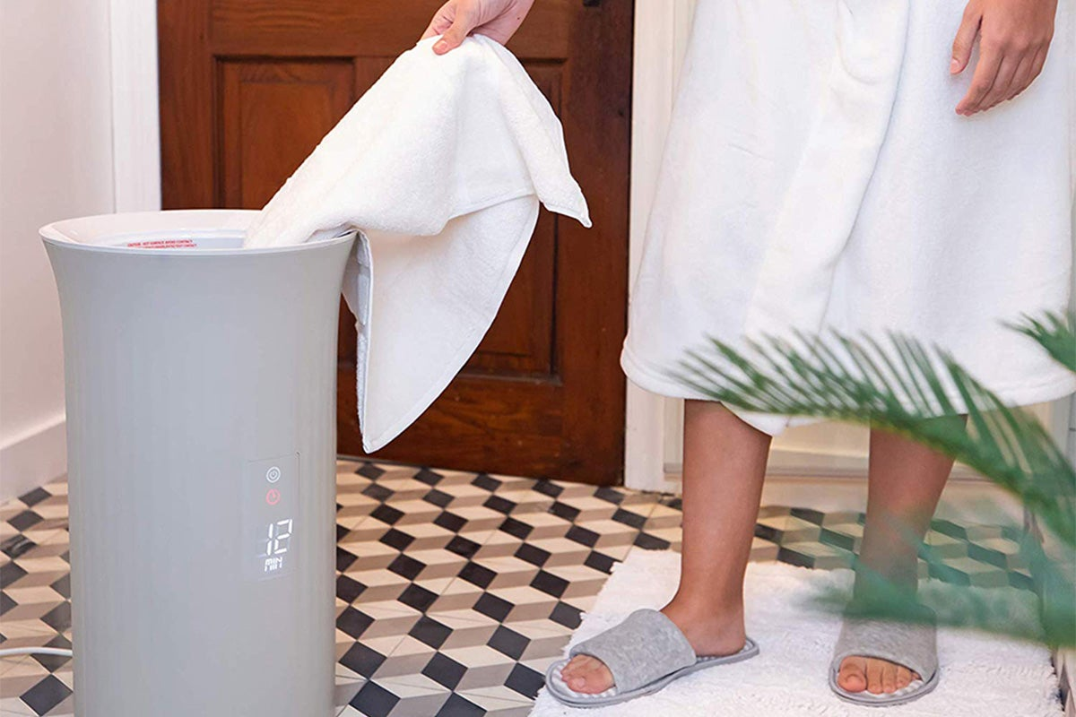 Person grabbing towel from towel warmer