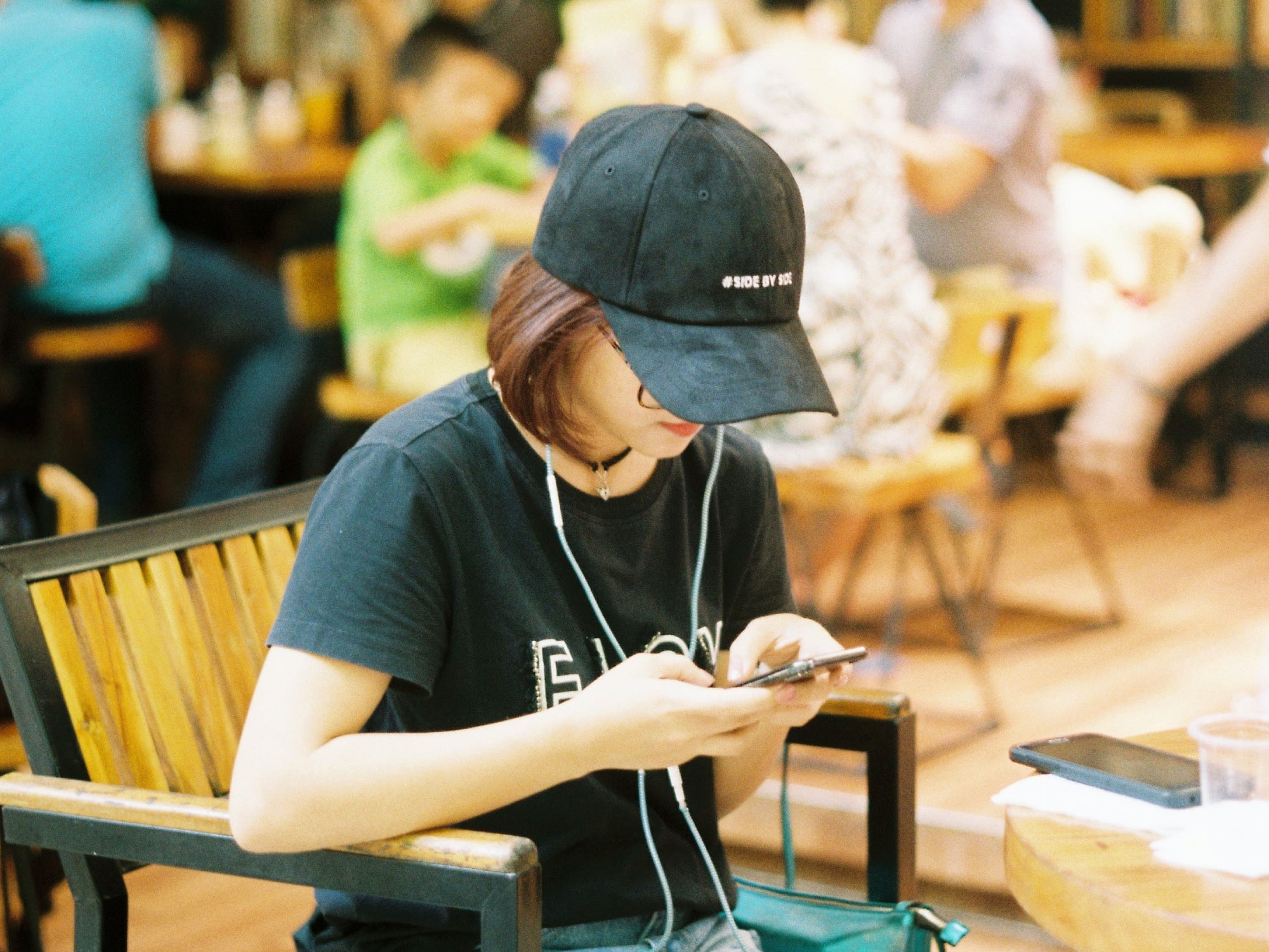 A person sitting at a coffee shop, using a phone while wearing headphones and a cap.