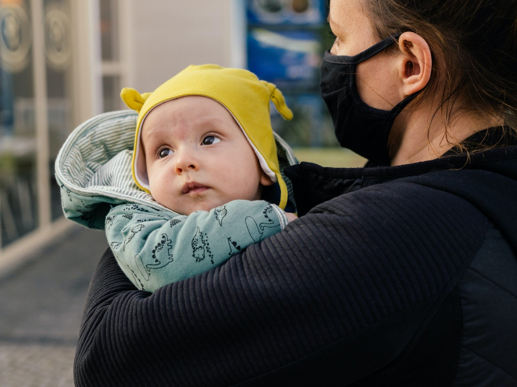 mother masked holding her baby