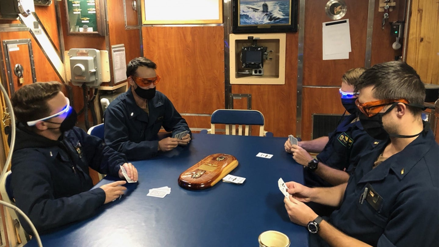 Sailors playing cards in orange and blue-light goggles