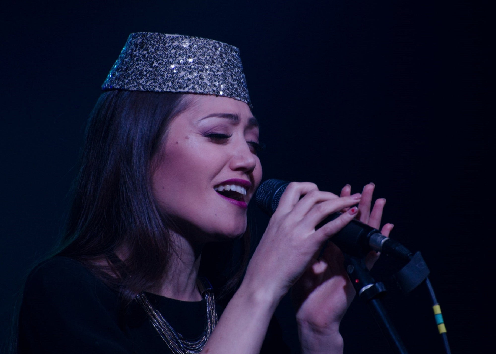 Person with long black hair and in silver sequin hat at microphone