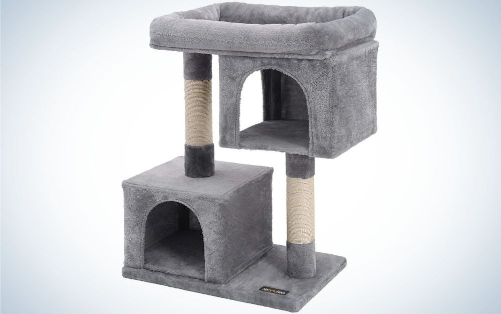 A grey cat house with two floors and in a square shape with a small door in front of them.