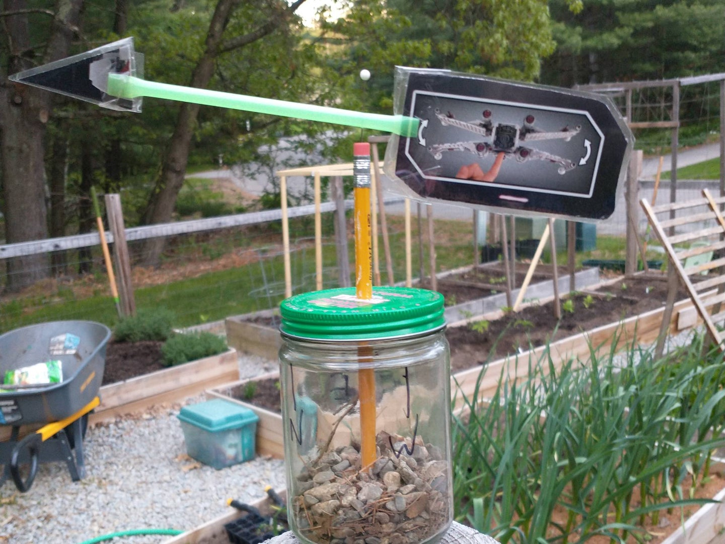A DIY weather vane made out of recycled materials, set up outside.