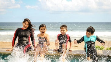 A woman and children splashing their feet in water with the best sunscreen