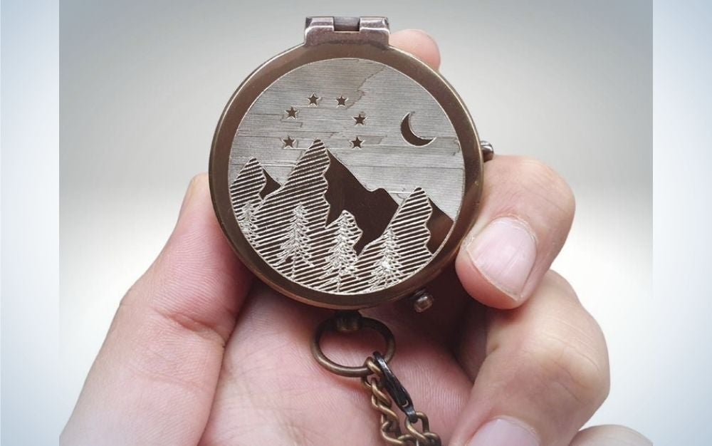 A hand of a person holding into his fingers a picture of a mountain and the moon into a clock shape and form.