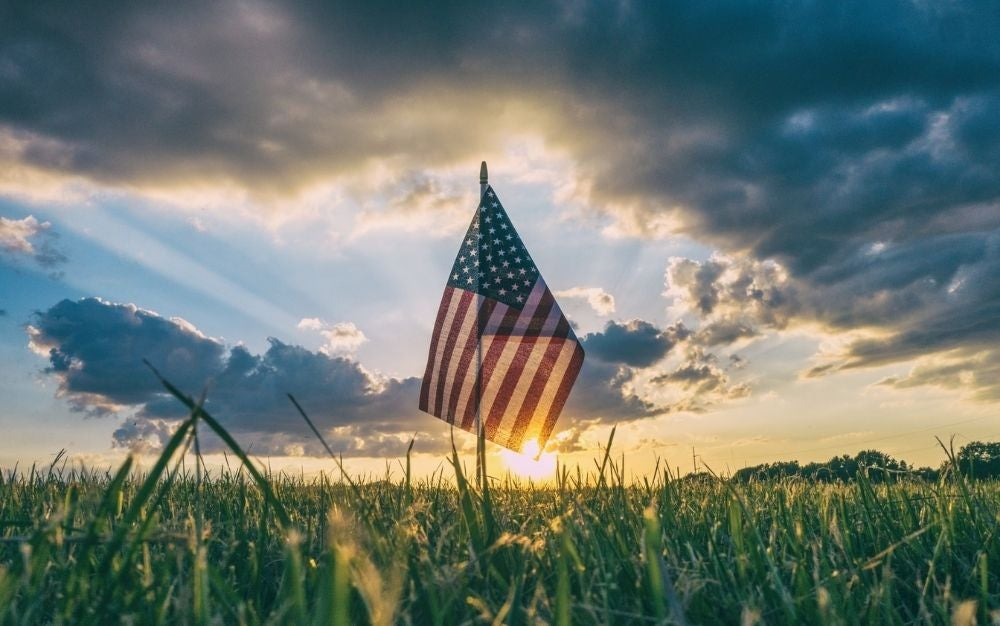 A USA flag waving under the sunset in a large green field.
