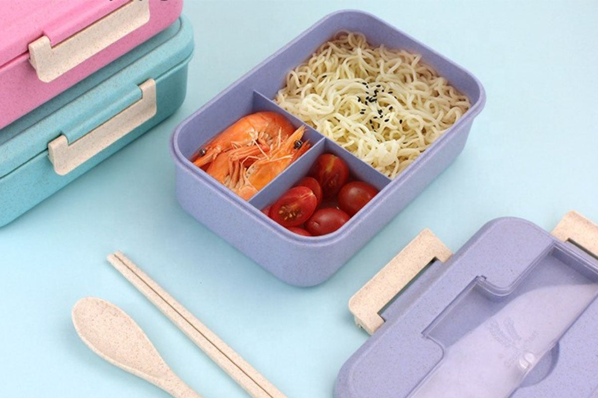 Lunchbox packed with food, next to wooden utensils.