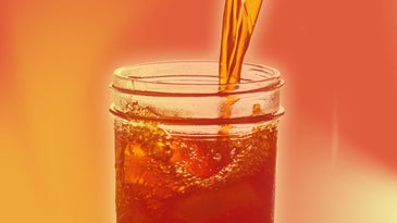 A cold drink like ice tea is poured into a glass with an orange/red overlay.