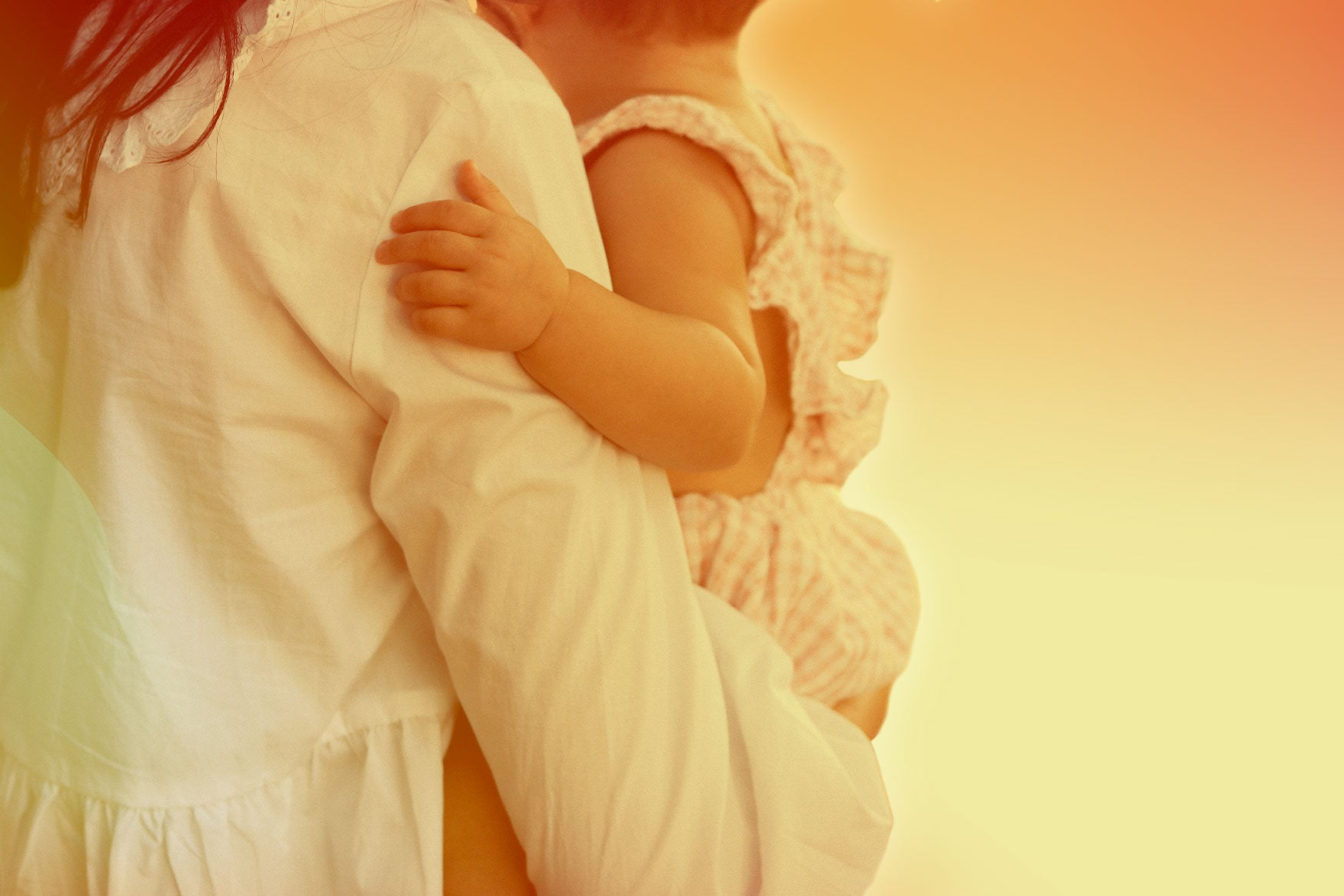 A person wearing a long-sleeved white shirt while holding a baby.
