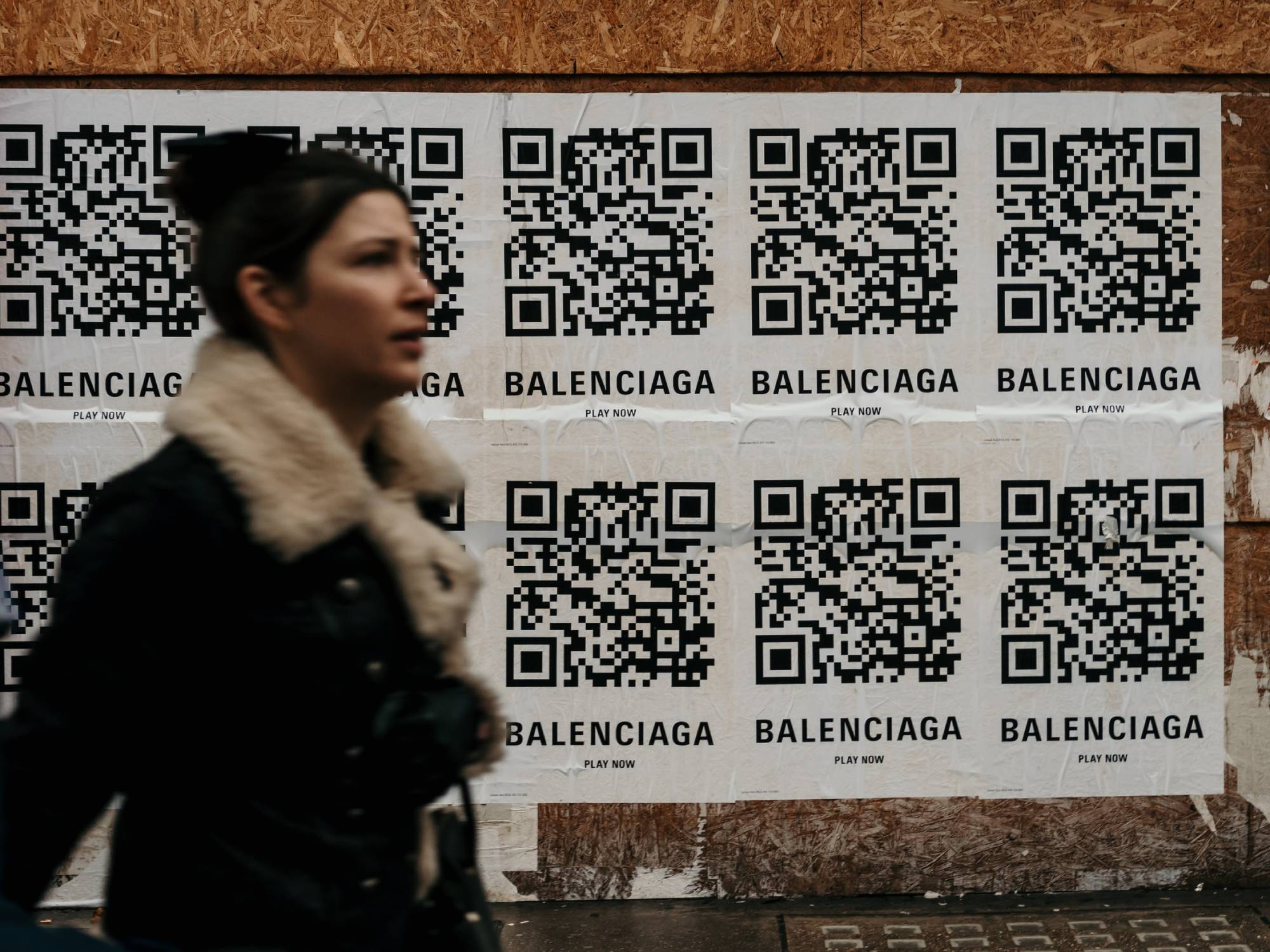 Person walking in front of posters with big QR codes