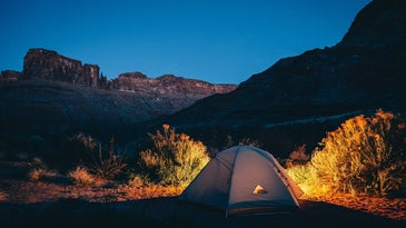 Tent lit by lanterns in a canyon at night