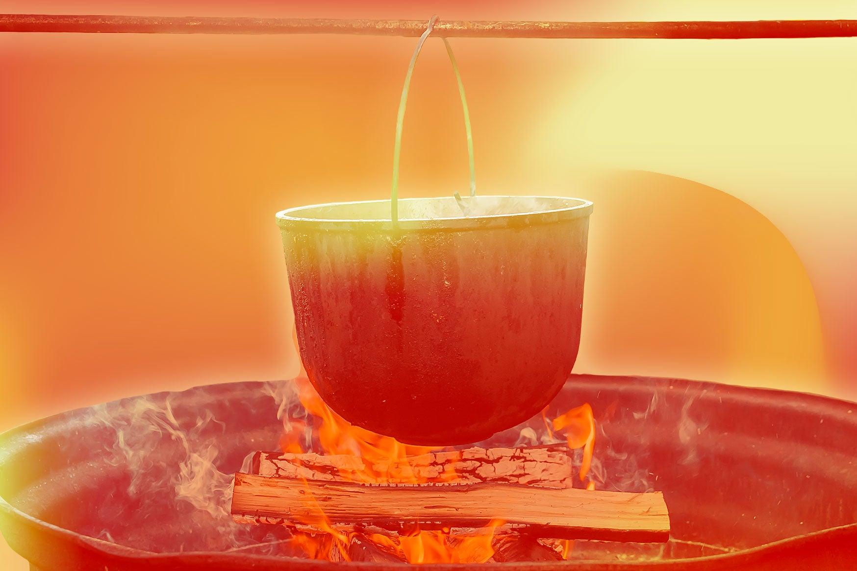 An iron pot on a spit above a cooking fire.