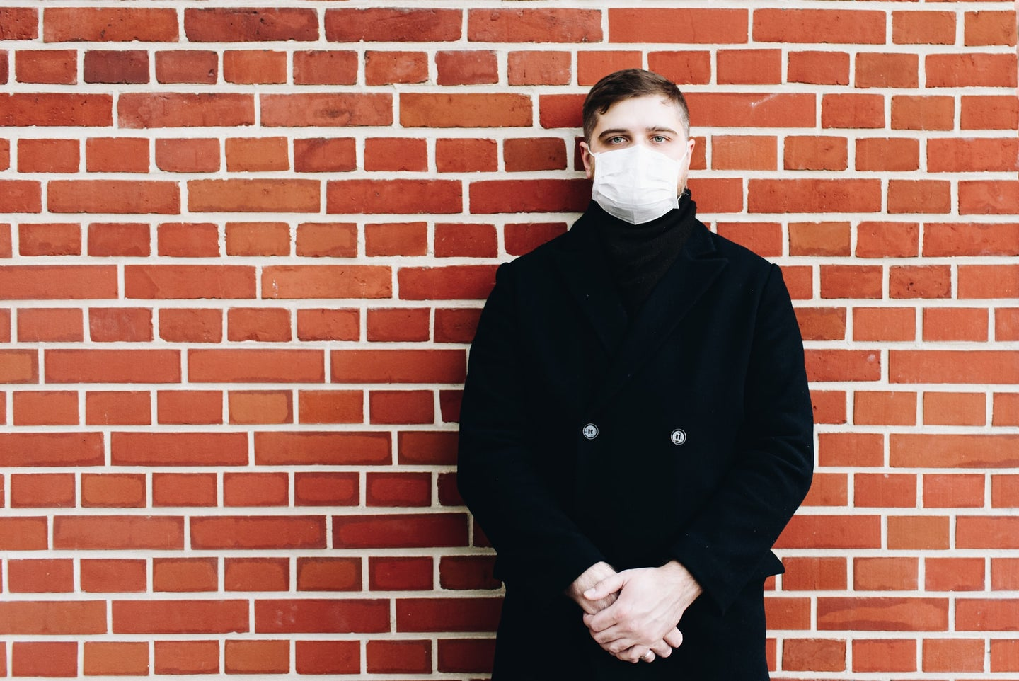 man in mask stands in front of brick wall