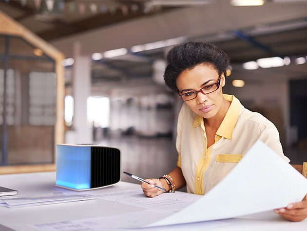 Woman working at desk with small AC unit.