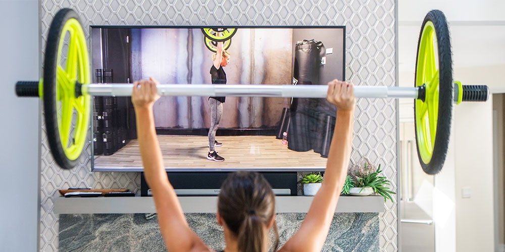 Woman lifting weights in front of TV.