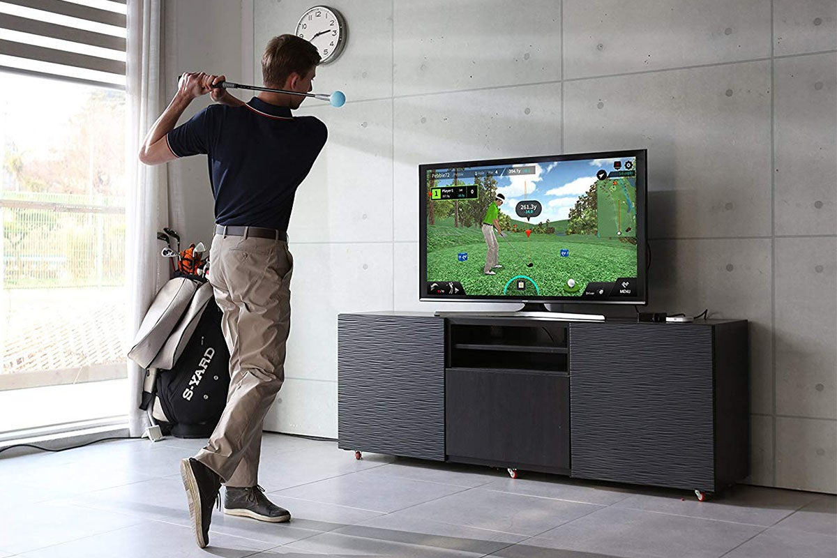 Man playing golf in front of TV.