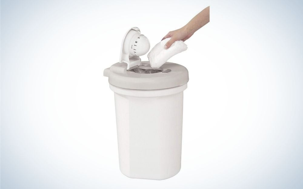 A cylindrical waste bin and all white plain and with a lid that opens from above and a hand that throws pampers inside it.