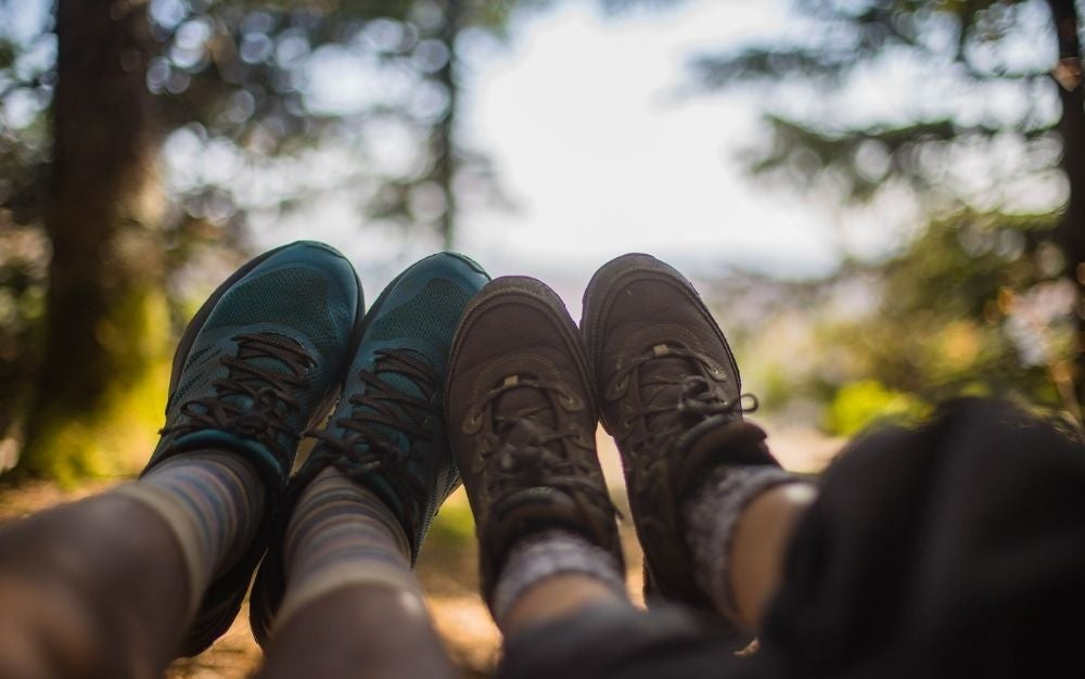 Two people wearing hiking boots, one blue and the other brown, and leaning close to each other.