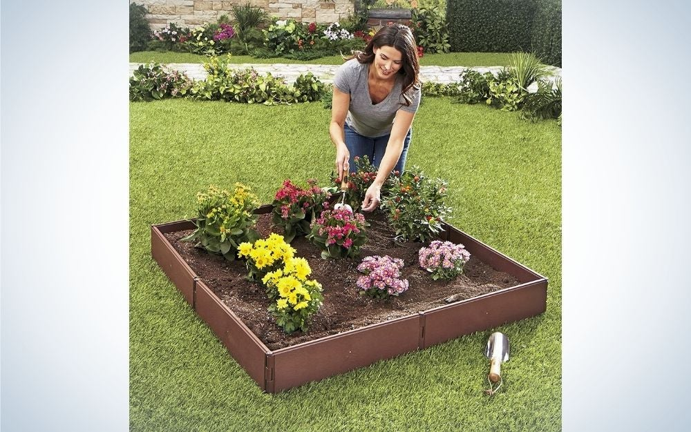 A woman taking care of her garden and flowers set in a square garden bed.
