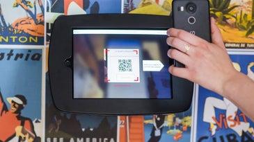 Hand holding phone scanning QR code