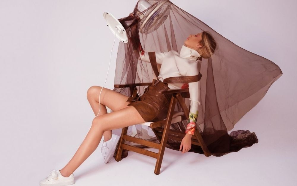 A woman is taking poses by sitting into a brown chair with a white fan into her fare and with a as well as covered her body with a piece of translucent brown color.