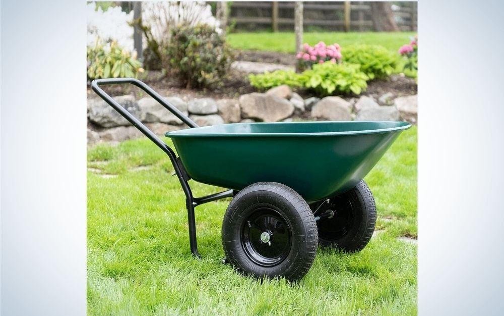 A small wheelbarrow in a green color with two black wheels standing over a grassy ground and flowers.
