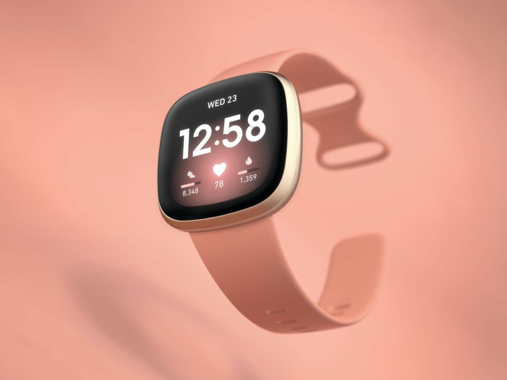 A Fitbit Versa 3 on a pale pink background.