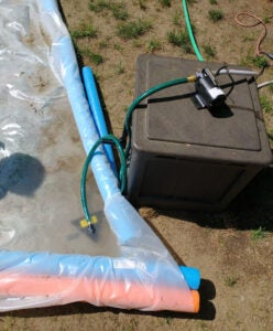 The pool at the end of a DIY slip and slide, with a water pump in position to recycle the water.
