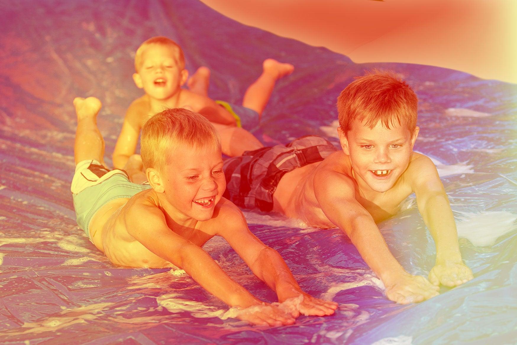 Three children sliding down a slip and slide.