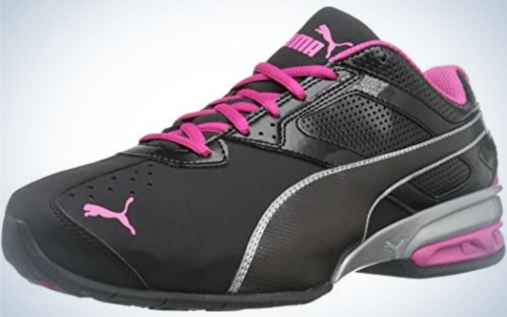 A black sneakers with pink laces and the pink brand mark on it.