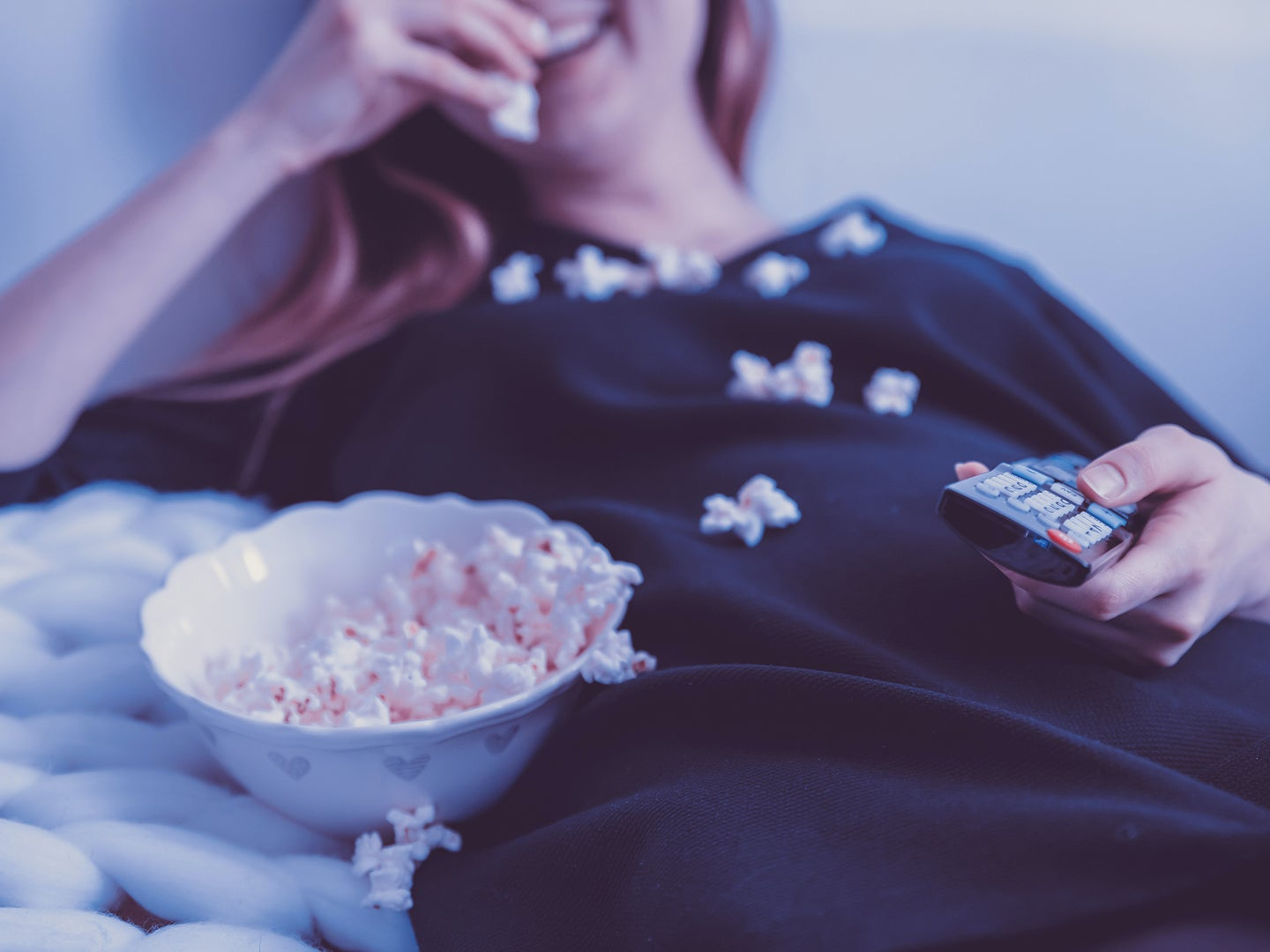 A woman lounging on a couch, eating a bowl of popcorn, while holding a TV remote with popcorn all over her chest.