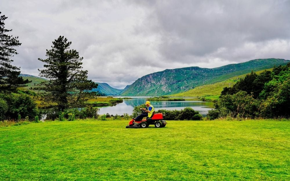 A man with a hat riding a four wheel lawn mower with black and red color into a green field all of grass in front of a lake.