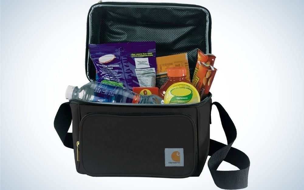 A small square shape black lunch bag with a zipper at the bottom of it and full with items in it.