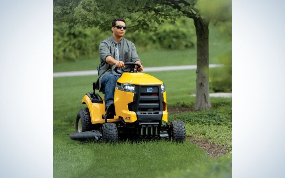 A man with eyes who drives a harvester on a green space with grass and flowers, which resembles an engine with four yellow and black tires.