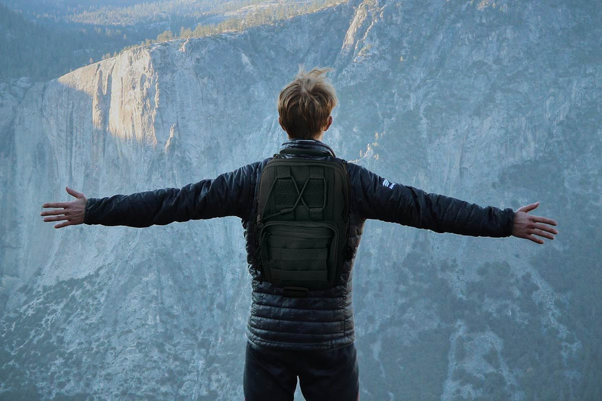 Man standing with arms open on mountain