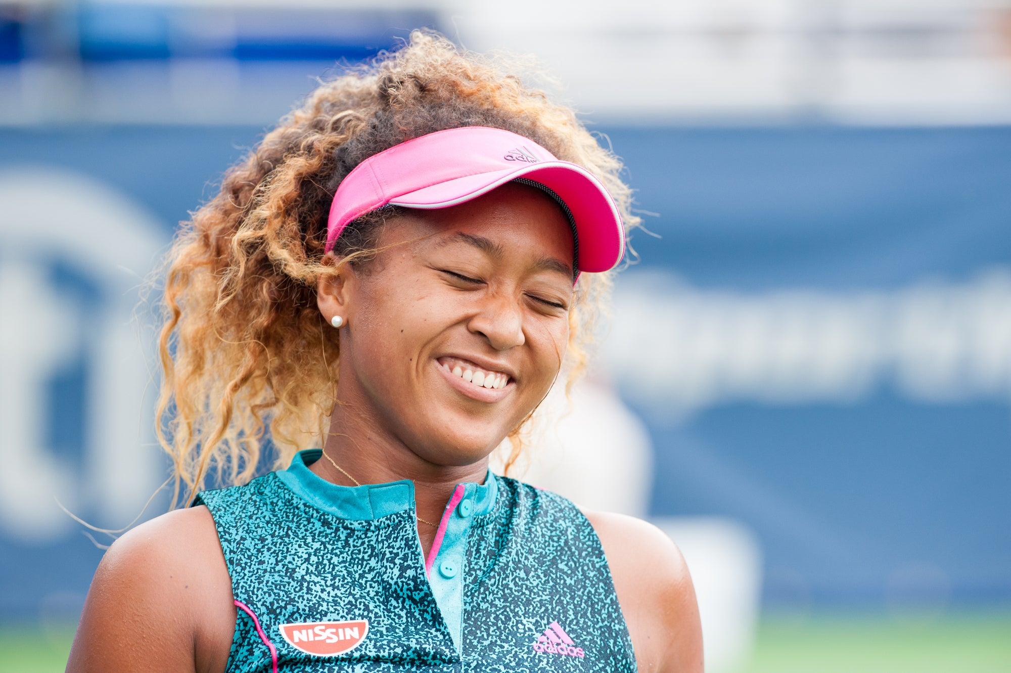 Naomi Osaka smiling on the tennis court in a pink visor