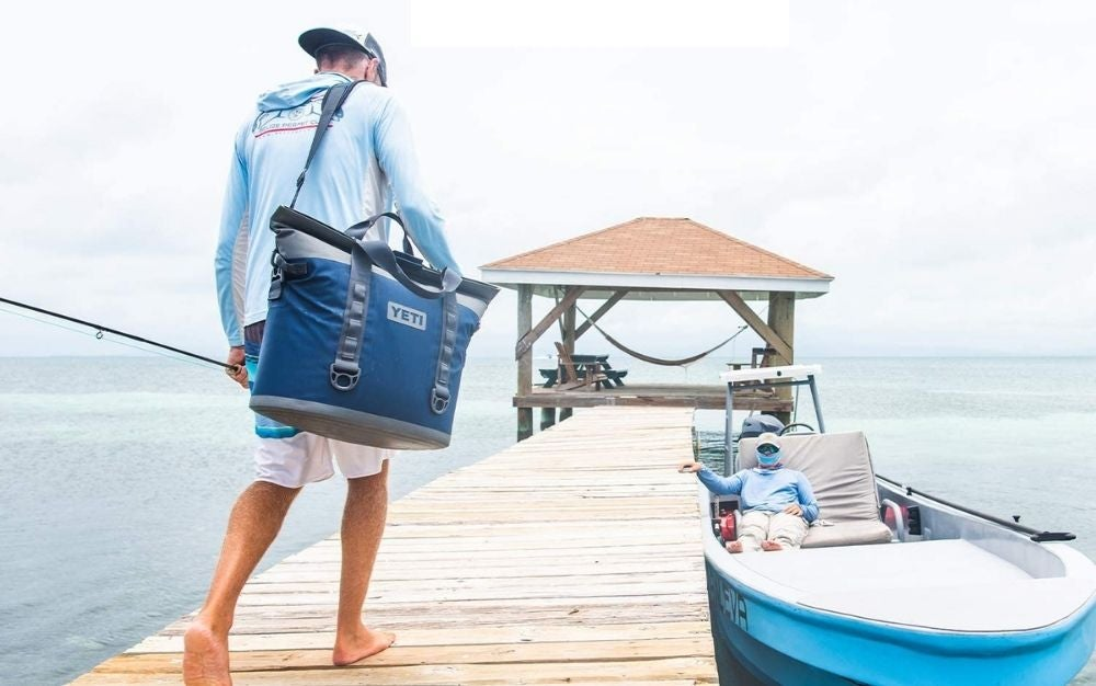 A man with shorts and with a hat and a big YETI bag walking into a wooden place through the sea.